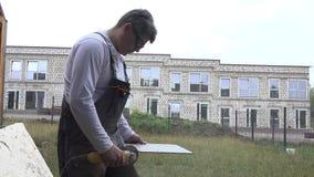 De vakman sneed muurtegel met draagbare hoekmolen stock videobeelden