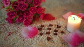 De valentijnskaart van de decoratielengte van bloemboeket, kaars het branden en nam bloemblaadjes toe stock footage