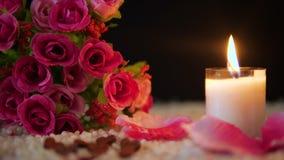De valentijnskaart van de decoratielengte van bloemboeket, kaars het branden en nam bloemblaadjes toe stock video