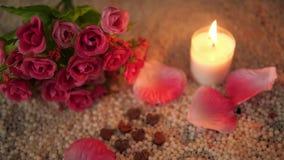 De valentijnskaart van de decoratielengte van bloemboeket, kaars het branden en nam bloemblaadjes toe stock videobeelden