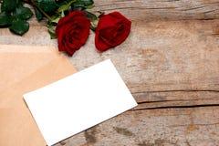 De valentijnskaart van de liefdebrief nam en in envelop op houten achtergrond toe royalty-vrije stock foto