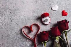 De valentijnskaartendag huwt me huwelijksverlovingsring in doos met rode rozen Stock Fotografie