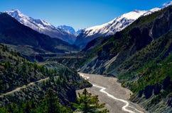 De vallei van de de bergrivier van Himalayagebergte met pieken op achtergrond stock fotografie