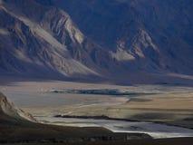 De vallei van de hooggebergterivier, gedeeltelijk verlichte stralen die zon, donkere hellingen plaatsen van pieken, Tibet, het Hi Royalty-vrije Stock Foto's