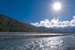 De vallei van de rivier onder heldere zonneschijn Stock Afbeeldingen