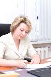 De van de bedrijfs middelbare leeftijd vrouw schrijft document Stock Foto's