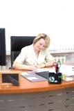 De van de bedrijfs middelbare leeftijd vrouw schrijft document Stock Afbeelding