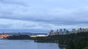 De Vancouver horizonte de la ciudad A.C. Canadá con las nubes móviles y tráfico a lo largo de Stanley Park Seawall en la hora azul metrajes