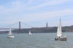 De varende boot en 25 DE Abril Bridge, Tagus-rivier van Lissabon Royalty-vrije Stock Foto's