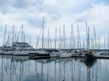 De varende jachten bevinden zich met zeilen dat in een kleine haven op een bewolkte dag worden verminderd stock foto's