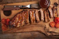 De varkensvleesribben in barbecuesaus en honing roosterden tomaten op een houten Raad Een grote snack aan bier op een rustieke ho Royalty-vrije Stock Fotografie