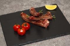 De varkensvleesribben in barbecuesaus en honing roosterden tomaten op een zwarte leischotel stock foto's