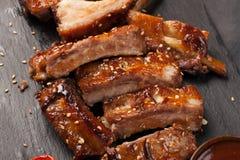 De varkensvleesribben in barbecuesaus en honing roosterden tomaten op een zwarte leischotel Een grote snack aan bier op een zwart Stock Fotografie