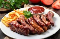 De varkensvleesribben, de aardappelgebraden gerechten en de tomatensaus, sluiten omhoog mening stock foto