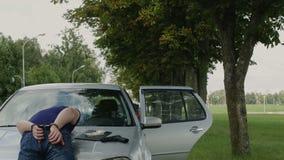 De vastgehouden misdadiger in handcuffs ligt op de kap van de auto stock video