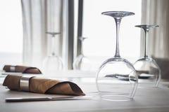 De vastgestelde dienst van de cateringslijst met tafelzilver, servet en glaswerk bij restaurant geschoten tegen venster Royalty-vrije Stock Afbeeldingen