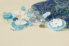 De veelkleurige parels, haken bloemen, blauw aquamarijngemmen en katoenen garen De blauwe, donkerblauwe en gele parels van Nice e Royalty-vrije Stock Afbeeldingen
