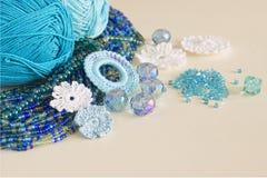 De veelkleurige parels, haken bloemen, blauw aquamarijngemmen en katoenen garen De blauwe, donkerblauwe en gele parels van Nice e Royalty-vrije Stock Fotografie