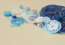De veelkleurige parels, haken bloemen, blauw aquamarijngemmen en katoenen garen De blauwe, donkerblauwe en gele parels van Nice e Stock Foto's
