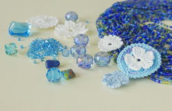 De veelkleurige parels, haken bloemen, blauw aquamarijngemmen en katoenen garen De blauwe, donkerblauwe en gele parels van Nice e Stock Foto