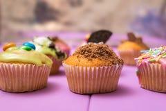 De veelvoudige die muffins met het multicolored berijpen, cacaopoeder en bonen, suikergoed en slagroom zijaanzicht worden verfraa Stock Foto
