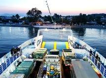 De veerboot nadert de kust bij dageraad stock afbeeldingen