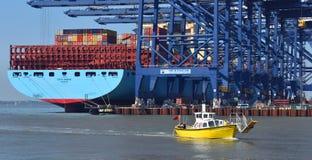 De veerboot over het Orwell-Estuarium gaat voorbij groot containerschip die bij Felixstowe-dokken worden geladen stock fotografie