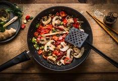 De veganist beweegt gebraden gerecht in pot op houten achtergrond, hoogste mening Gehakte geroosterde groenten in pan Aziatisch v royalty-vrije stock afbeeldingen