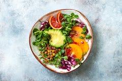 De veganist, detox de kom van Boedha met kurkuma roosterde kekers, greens, avocado, dadelpruim, bloedsinaasappel, noten en granaa stock foto