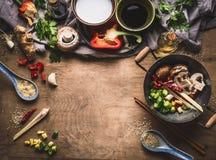 De vegetariër beweegt gebraden gerecht kokende voorbereiding op houten achtergrond met diverse groenten, wok, kokosmelk, zaden en stock foto