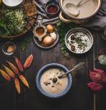 De vegetarische kom van de kastanjes romige soep op de donkere rustieke achtergrond van de keukenlijst met het koken van pot, ing Royalty-vrije Stock Foto's