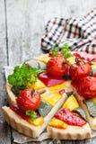 De vegetarische quiche met gekleurde peper en kersentomaten streeft na royalty-vrije stock afbeelding