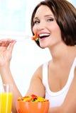 De vegetarische vrouw eet nuttig plantaardig voedsel Royalty-vrije Stock Afbeeldingen