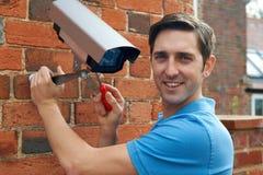De Veiligheidscamera van de mensenmontage aan Huismuur Royalty-vrije Stock Fotografie