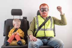 De Veiligheidsgordel van de auto Een gelukkig kind zit in autoleunstoel naast de mens met rode haar, baard en snor in geel overhe Royalty-vrije Stock Foto