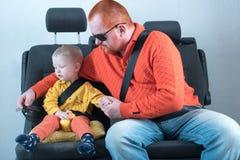 De Veiligheidsgordel van de auto Een gelukkig kind zit in autoleunstoel naast de mens met rode haar, baard en snor in geel overhe Stock Afbeeldingen
