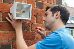 De Veiligheidslicht van de mensenmontage aan Muur van Huis Stock Afbeelding