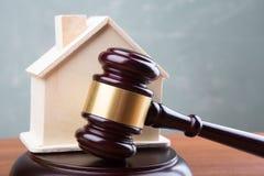De veilingsconcept van de onroerende goederenverkoop - de hamer en het huis modelleren op de houten lijst royalty-vrije stock afbeeldingen