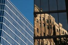 De vensterbezinningen benadrukken dramatisch oude en nieuwe highrise gebouwen Royalty-vrije Stock Afbeeldingen