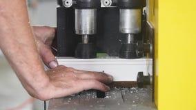 De vensters en de deuren productie van pvc Arbeider die het profiel van pvc met cirkelzaag snijden Snijdend pvc-profiel met cirke stock videobeelden