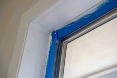 De vensterversiering behandelde met blauwe schilders band tijdens de verbeteringen van de huisvernieuwing tijdens het schilderen royalty-vrije stock foto