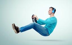 De ventilator van de mensenmuziek in hoofdtelefoons drijft een auto met een stuurwiel Royalty-vrije Stock Afbeelding