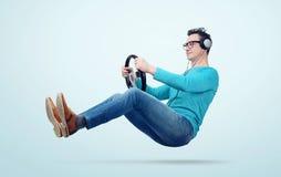 De ventilator van de mensenmuziek in hoofdtelefoons drijft een auto met een stuurwiel Royalty-vrije Stock Fotografie
