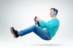 De ventilator van de mensenmuziek in hoofdtelefoons drijft een auto met een stuurwiel Royalty-vrije Stock Foto's