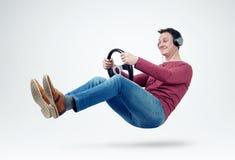 De ventilator van de mensenmuziek in hoofdtelefoons drijft een auto met een stuurwiel Royalty-vrije Stock Foto