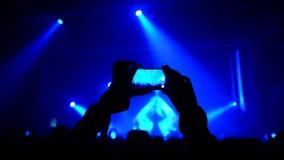 De ventilators die hun handen golven en houden de telefoon met digitale vertoningen stock videobeelden