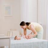 De veranderende baby?s luier van de moeder op bed Stock Afbeelding