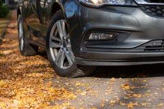 De verandering van de seizoenband Auto met nieuwe de winterbanden op de weg voor de herfstbladeren stock foto