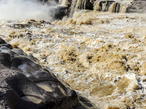 De veranderlijke wateren van de Gele rivier met geërodeerde rotsen Stock Afbeelding