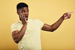 De verbaasde emotionele jonge donker-gevilde mens kleedde zich in modieuze T-shirt stock foto